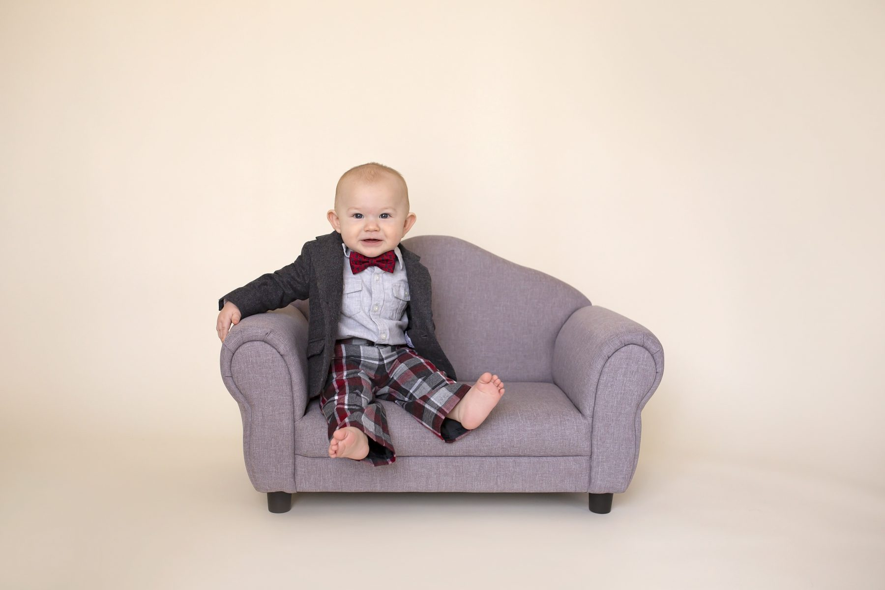 8 month old sitting on a tiny couch while wearing a suit and smiling