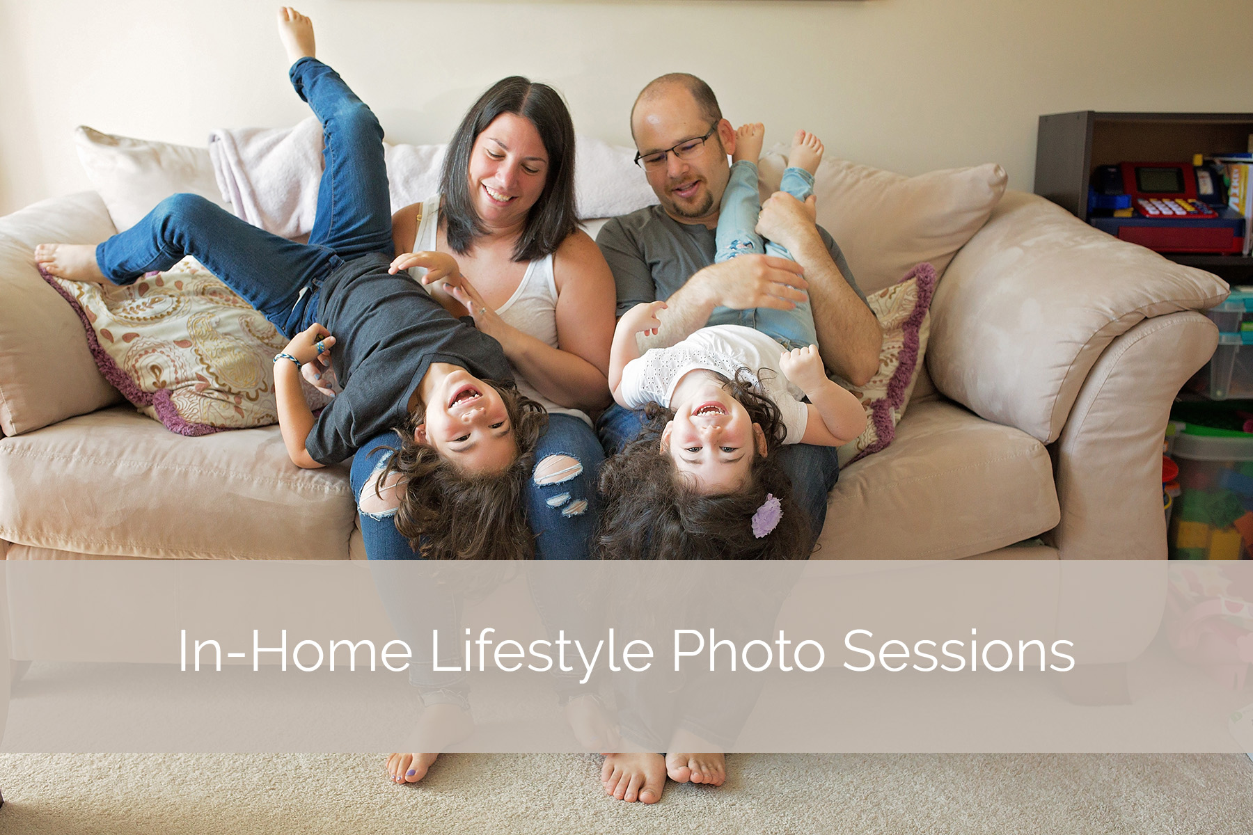 mom dad son and daughter all smiling on couch while parents hold kids upsidedown